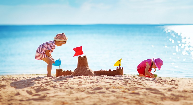 kids on beach with sandcastles