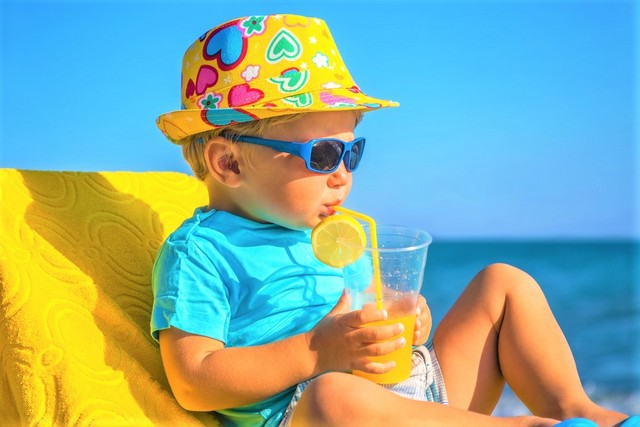 child on the beach with a drink in a yellow sun hat
