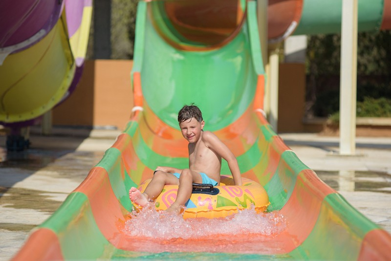 little boy going down a water slide
