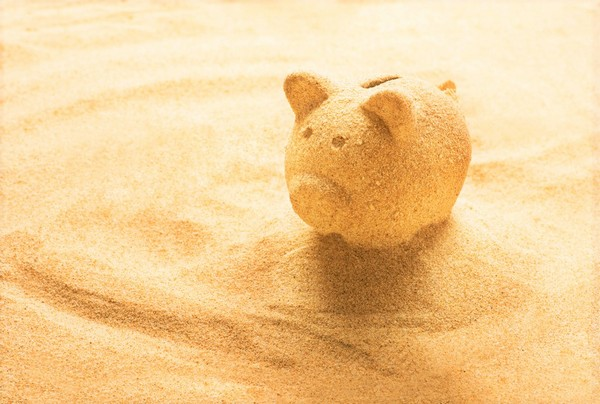 all inclusive versus self catered piggy bank made of sand