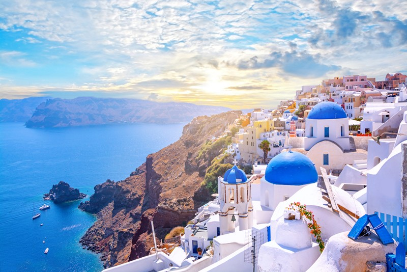 Beautiful Oia town on Santorini island, Greece. Traditional white architecture and greek orthodox churches with blue domes over the Caldera, Aegean sea