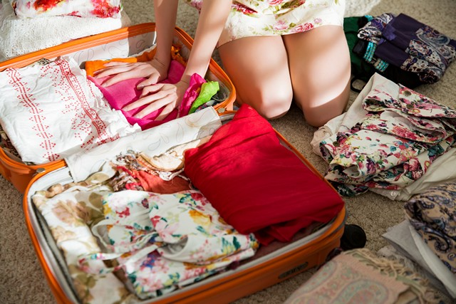 women with new clothes in a suitcase