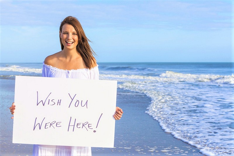 woman holding 'wish you were here' sign
