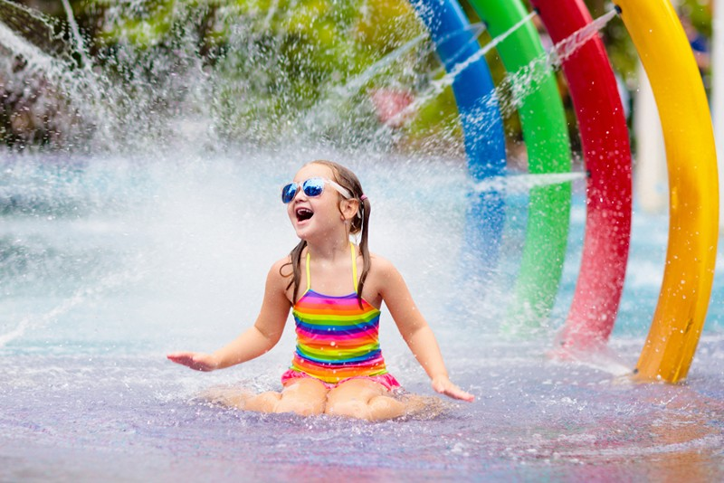little girl playing in a water park with rainbow colours