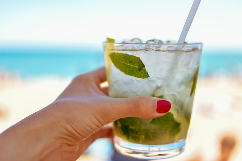 Woman holding a cocktail on the beach, Nerja