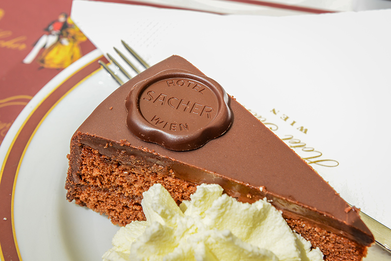 Original Sacher Torte with cream and fork at Sacher Cafe, Vienna, Austria