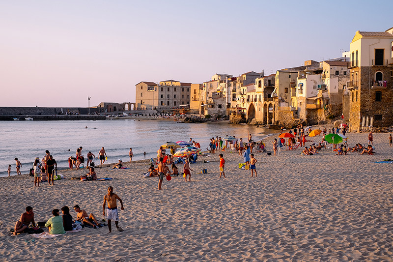Tourists enjoy the beach at sunset in Cefala Sicily