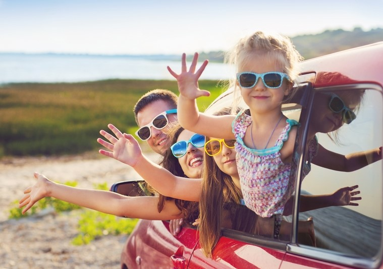 Family waving from car on holiday