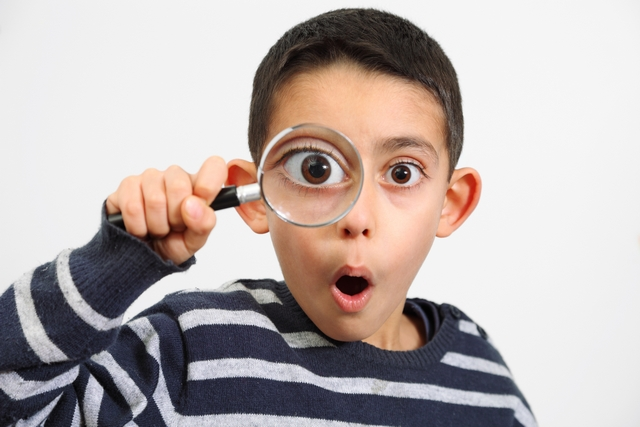 young boy with a magnifying glass