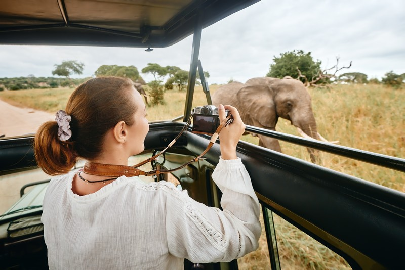 Safari in Kenya, woman taking photo of Elephant
