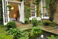 Apartment in United Kingdom, London: The bedroom overlooks this garden and pond.