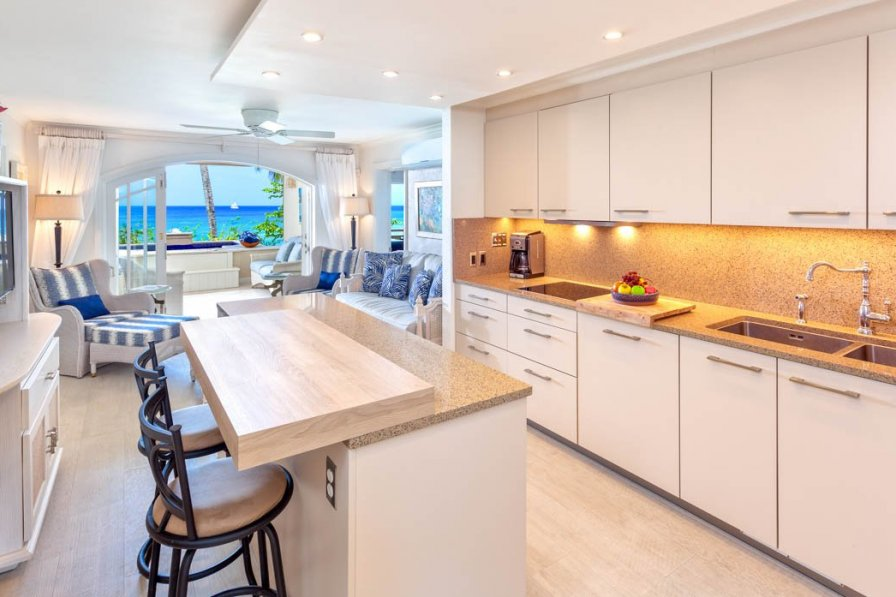 Villa in Barbados, Holetown, St. James. Inside open plan kitchen leading on to living area and then decking area outside with the beach in the far background