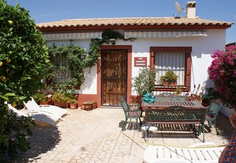 Village House in Spain, Busot: Front patio of Bungalow with table and chairs and sun beds.
