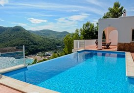 Ibiza villa with infinity pool looking at bay and beach.